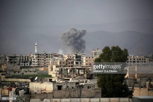 Smoke billows following Syrian government bombardment in Arbin in the rebelheld enclave of Eastern Ghouta on March 10 2018 Syrian regime forces cut...