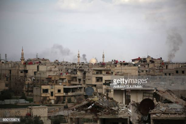 Smoke billows following Syrian government bombardment on Kafr Batna in the besieged Eastern Ghouta region on the outskirts of the capital Damascus on...