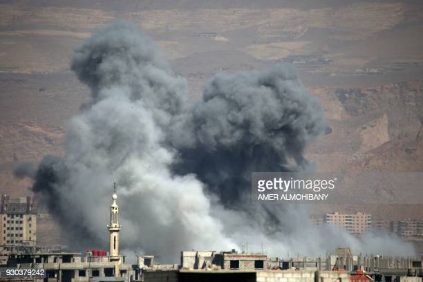 TOPSHOT Smoke billows following Syrian government bombardment on the rebelcontrolled town of Arbin in the besieged Eastern Ghouta region on the...