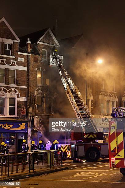 Smoke billows from a building in Clapham Junction on August 8 2011 in London England Sporadic looting and clashes with police continue for a third...