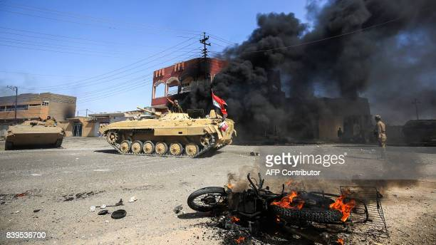 TOPSHOT Smoke billows from a burning building and motorcycle as Iraqi forces' armoured vehicles advances through a street in the town of Tal Afar...