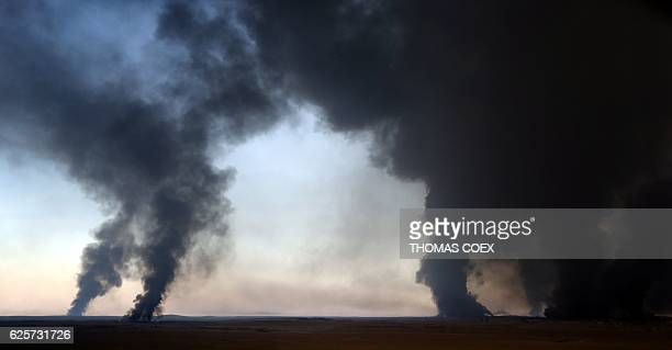 Smoke billows from a burning oil well, set ablaze by retreating Islamic State group's jihadists, in Qayyarah, some 60 kilometres south of Mosul on...