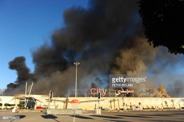 Smoke billows from a French and a Tunisian supermarket on January 15 2011 in La Gazella city near Tunis Tunisia's speaker of parliament took power on...