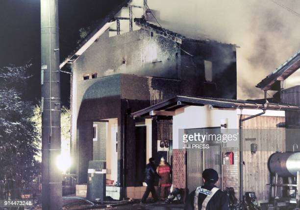 Smoke billows from a house as Japanese policemen and firefighters inspect it after a Japan's Ground SelfDefense Force's AH64 Apache attack helicopter...