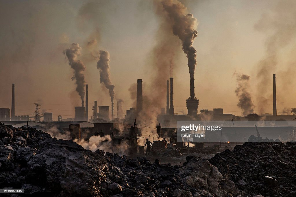 Smoke billows from a large steel plant as a Chinese labourer works at an unauthorized steel factory, foreground, on November 4, 2016 in Inner Mongolia, China. To meet China's targets to slash emissions of carbon dioxide, authorities are pushing to shut down privately owned steel, coal, and other high-polluting factories scattered across rural areas. In many cases, factory owners say they pay informal 'fines' to local inspectors and then re-open. The enforcement comes as the future of U.S. support for the 2015 Paris Agreement is in question, leaving China poised as an unlikely leader in the international effort against climate change. U.S. president-elect Donald Trump has sent mixed signals about whether he will withdraw the U.S. from commitments to curb greenhouse gases that, according to scientists, are causing the earth's temperature to rise. Trump once declared that the concept of global warming was 'created' by China in order to hurt U.S. manufacturing. China's leadership has stated that any change in U.S. climate policy will not affect its commitment to implement the climate action plan. While the world's biggest polluter, China is also a global leader in establishing renewable energy sources such as wind and solar power.