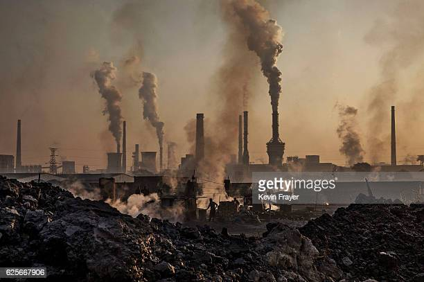 Smoke billows from a large steel plant as a Chinese labourer works at an unauthorized steel factory, foreground, on November 4, 2016 in Inner...