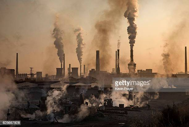 Smoke billows from a large steel plant as a Chinese labourer works at an unauthorized steel factory foreground on November 4 2016 in Inner Mongolia...