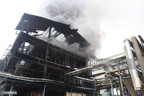 Smoke billows from a partially burned structure of a pharmaceutical factory after a fire broke out following an explosion in Dera Bassi some 24 kms...