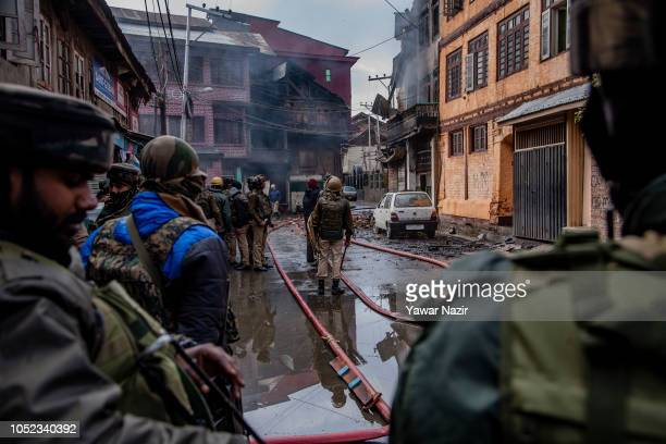 Smoke billows from a ravaged residential house as Indian government forces stand guard after a gun battle between Indian government forces and...