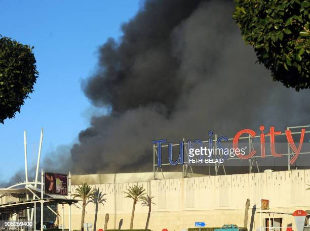 Smoke billows from a Tunisian supermarket on January 15 2011 in La Gazella city near Tunis Tunisia's speaker of parliament took power on todya amid...