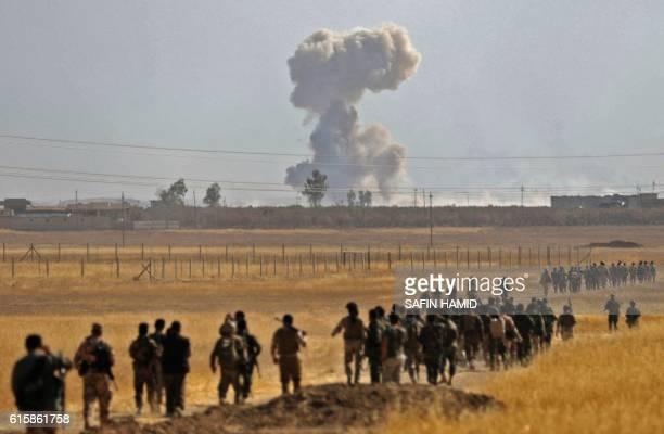 TOPSHOT Smoke billows from an area near the Iraqi town of Nawaran some 10km north east of Mosul as Iraqi Kurdish Peshmerga fighters march down a dirt...