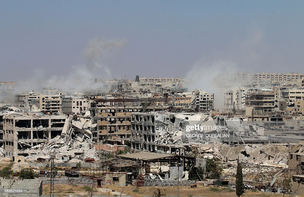 TOPSHOT - Smoke billows from buildings during an operation by Syrian government forces to retake control of the rebel-held district of Leramun, on the northwest outskirts of Aleppo, on July 26, 2016. The Syrian Observatory for Human Rights said on July 26 loyalist troops had full control of the Leramun district after heavy clashes, and reported fighting for neighbouring Bani Zeid, which is also held by rebels. / AFP / GEORGE