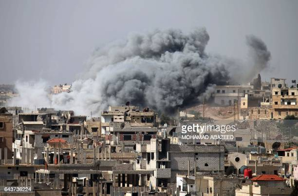 Smoke billows from buildings following reported air strikes on the southern Syrian city of Daraa on February 22 2017 / AFP / MOHAMAD ABAZEED