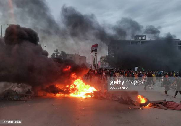 Smoke billows from burning tyres amid clashes between Iraqi anti-government protesters and supporters of firebrand Shiite cleric Moqtada Sadr, in the...