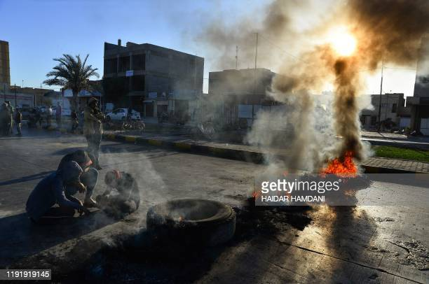 smoke billows from burning tyres as angry Iraqi demonstrators block a road in the central shrine city of Najaf on January 5 to protest turning the...