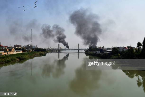 Smoke billows from burning tyres blocking a bridge over the Euphrates River in the centre of the southern Iraqi city of Nasiriyah where demonstrators...