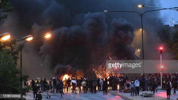 Smoke billows from burning tyres pallets and fireworks as a few hundred protesters riot in the Rosengard neighbourhood of Malmo Sweden on August 28...