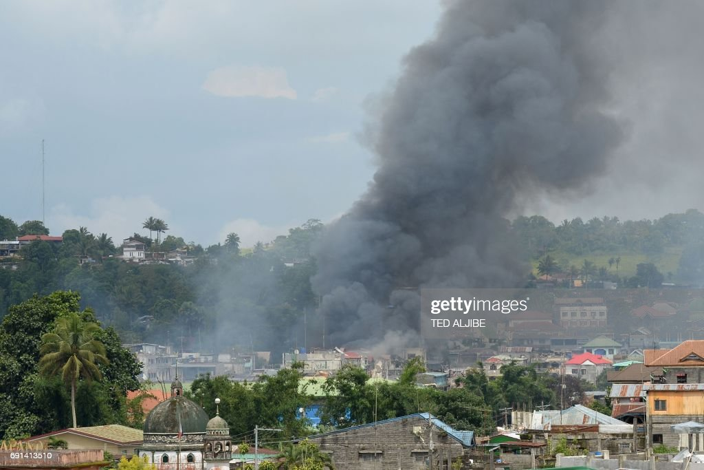 Smoke billows from houses after aerial bombings by Philippine Airforce planes on Islamist militant positions in Marawi, on the southern island of Mindanao on June 2, 2017. Militants have destroyed two tanks and damaged two others in a battle with Philippine security forces over a southern city that has claimed nearly 200 lives, the military said on June 2. /