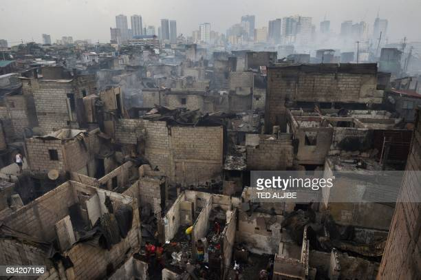 TOPSHOT Smoke billows from houses gutted by a fire overnight in an informal settlers area near the south harbour port in Manila on February 8 2017...