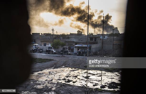 TOPSHOT Smoke billows from Islamic State positions as a convoy from the Iraqi Special Forces 2nd division move into position during fighting in the...