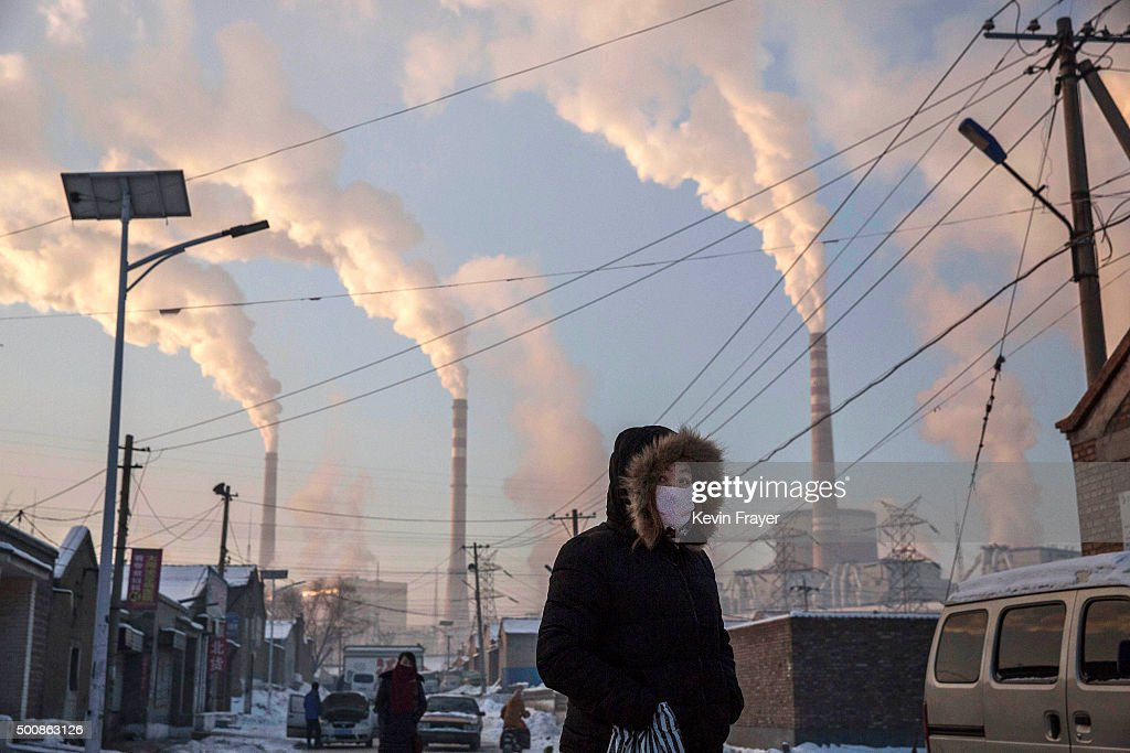 Smoke billows from stacks as a Chinese woman wears as mask while walking in a neighborhood next to a coal fired power plant on November 26, 2015 in Shanxi, China. A history of heavy dependence on burning coal for energy has made China the source of nearly a third of the world's total carbon dioxide (CO2) emissions, the toxic pollutants widely cited by scientists and environmentalists as the primary cause of global warming. China's government has publicly set 2030 as a deadline to reach the country's emissions peak, and data suggest the country's coal consumption is already in decline. The governments of more than 190 countries are expected to sign an agreement in Paris to set targets on reducing carbon emissions in an attempt to forge a new global agreement on climate change.