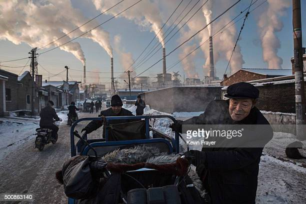 Smoke billows from stacks as Chinese men pull a tricycle in a neighborhood next to a coal fired power plant on November 26 2015 in Shanxi China A...