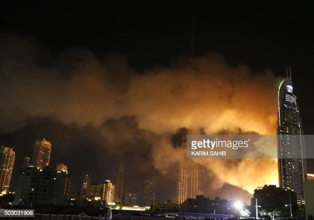 Smoke billows from the Address Downtown Hotel after it caught on fire hours earlier past fireworks near the Burj Khalifa the world's tallest tower in...