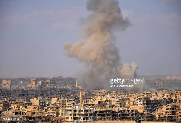 Smoke billows from the eastern Syrian city of Deir Ezzor during an operation by Syrian government forces against Islamic State group jihadists on...