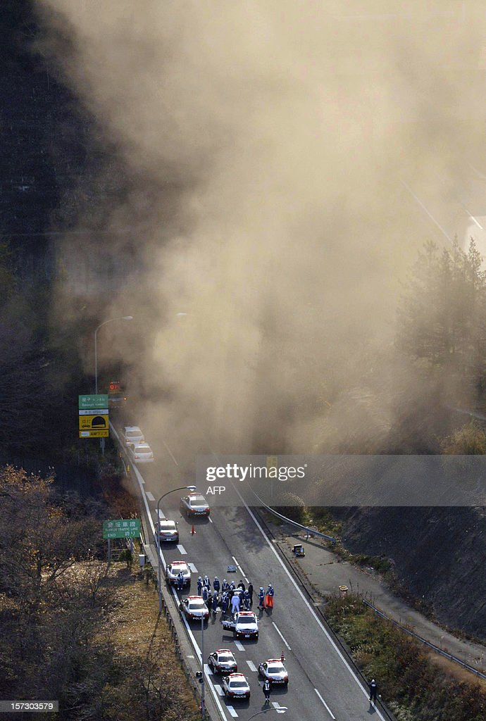 Smoke billows from the entrance of the collapsed Sasago tunnel as police and fire workers (bottom) gather in preparation for their rescue operation on the Chuo expressway in Koshu city, Yamanashi prefecture, some 80-kilometre west of Tokyo on December 2, 2012. At least seven people are missing after concrete ceiling panels along a section of highway tunnel collapsed in Japan. The accident occurred on Tokyo-bound lanes inside the Sasago tunnel on the Chuo Expressway, some 80 kilometres (50 miles) west of the capital, at around 8:00 am on December 2, an official at the expressway traffic police said. ==JAPAN OUT== AFP PHOTO / Motoki Nakashima / YOMIURI