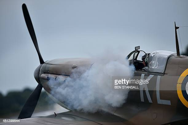 Smoke billows from the exhaust pipes of a Spitfire aircraft as the engine is started ahead of take off from Biggin Hill airfield in Kent on August 18...