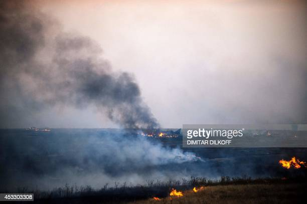 Smoke billows from the flaming debris of a crashed Ukrainian fighter jet near the village of Zhdanivka some 40 kilometres northeast of the rebel...