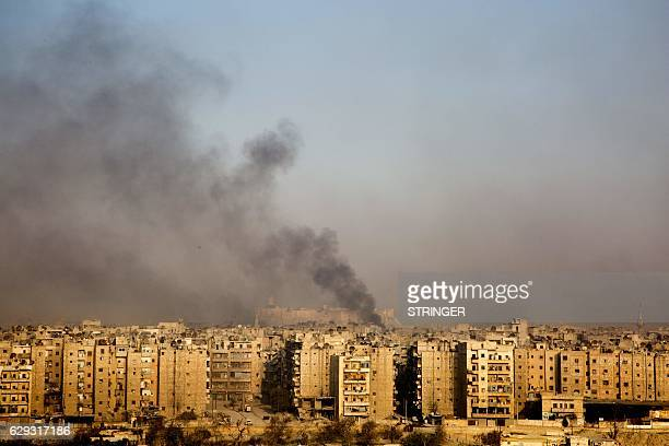 TOPSHOT Smoke billows from the former rebelheld district of Bustan alQasr in Aleppo on December 12 during an operation by Syrian government forces to...