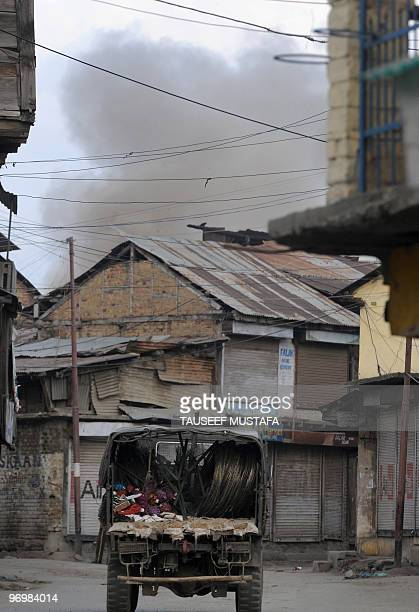 Smoke billows from the house where suspected militants are holed up during a gunbattle between Indian troops and alleged Muslim militants in Sopore,...