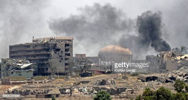 Smoke billows in a neighbourhood of west Mosul's near AlShifa hospital on May 30 2017 during ongoing battles between Iraqi forces to retake the city...