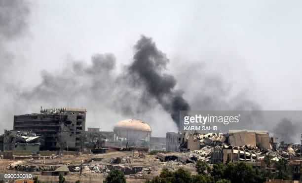 TOPSHOT Smoke billows in a neighbourhood of west Mosul's near AlShifa hospital on May 30 2017 during ongoing battles between Iraqi forces to retake...