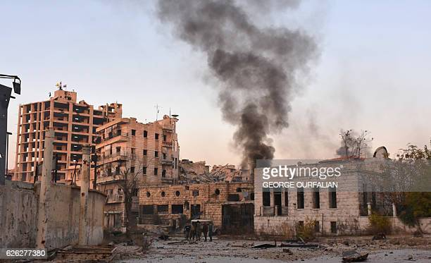 TOPSHOT Smoke billows in Aleppo's Bustan alBasha neighbourhood on November 28 during Syrian progovernment forces assault to retake the entire...