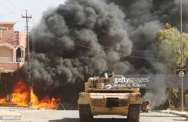 Smoke billows in the background as an Iraqi forces' tank advances through a street in the town of Tal Afar west of Mosul after the Iraqi government...