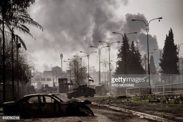 Smoke billows in the background as Iraqi forces clash with Islamic State group fighters in Mosul on March 5 during an offensive to retake the western...