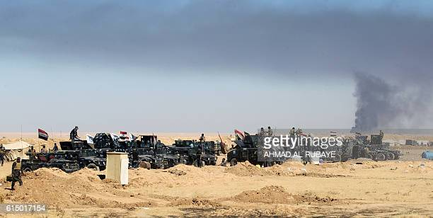 Smoke billows in the background as Iraqi forces gather at the Qayyarah military base about 60 kilometres south of Mosul on October 16 as they prepare...