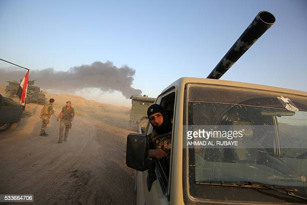 Smoke billows in the background as Iraqi progovernment forces advance towards the city of Fallujah on May 23 as part of a major assault to retake the...