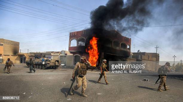 Smoke billows in the background as members of the Iraqi forces advance through a street in the town of Tal Afar west of Mosul after the Iraqi...