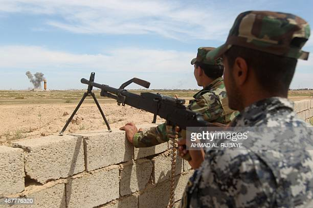 Smoke billows in the background as members of the Iraqi government forces hold a position on the western outskirts of Tikrit on March 27 during a...
