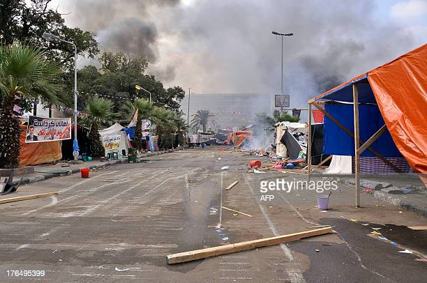 Smoke billows in the background as the protest camp set up by supporters of Egypt's deposed president Mohammed Morsi in Cairo's Al-Nahda square looks...
