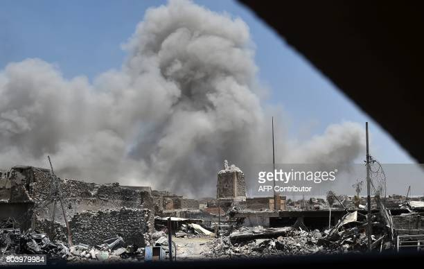 Smoke billows in the background behind the base of Mosul's destroyed ancient leaning minaret known as the Hadba in the Old City on June 30 after the...