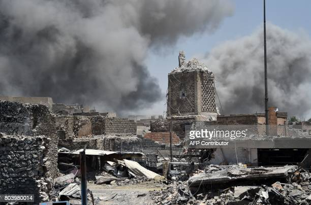 TOPSHOT Smoke billows in the background behind the base of Mosul's destroyed ancient leaning minaret known as the 'Hadba' in the Old City on June 30...