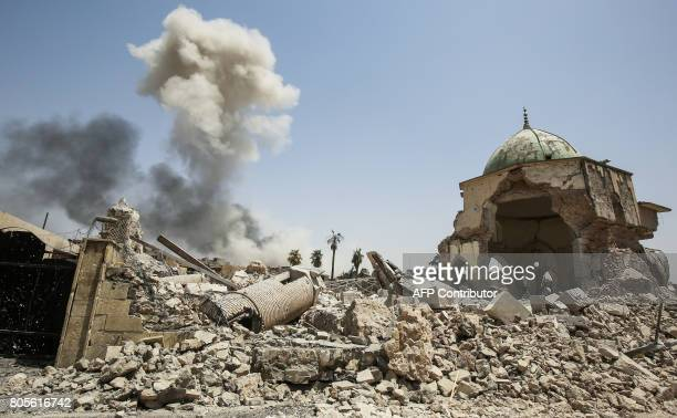 TOPSHOT Smoke billows in the background behind the remains of the destroyed leaning minaret known as the 'Hadba' and AlNuri Mosque in the Old City of...