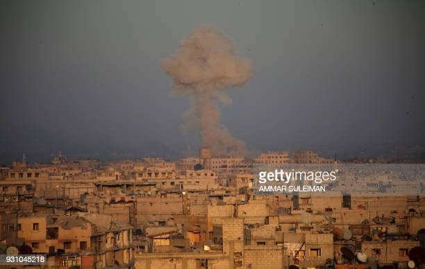 TOPSHOT Smoke billows in Zamalka in the Syrian rebel enclave of Eastern Ghouta on the outskirts of Damascu during reported shelling by Syrian...