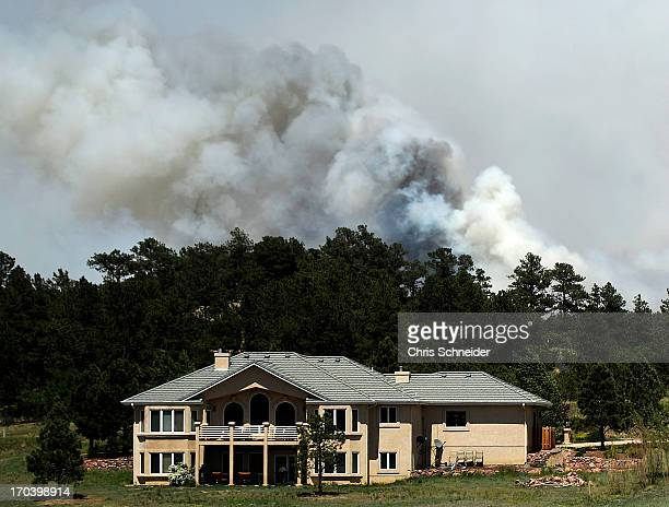 Smoke billows near a home from the Black Forest Fire on June 12 2013 north of Colorado Springs Colorado The fire has reportedly burned 80 to 100...