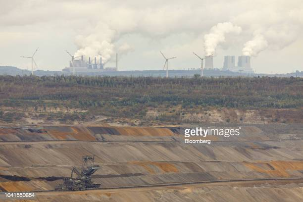 Smoke billows on the horizon from Frimmersdorf left and Neurath coalpowered plants operated by RWE as a giant excavator operates at the open pit...