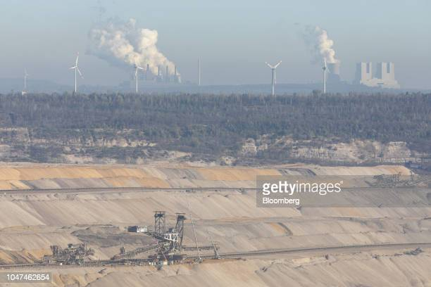 Smoke billows on the horizon from Frimmersdorf left and Neurath coalpowered plants operated by RWE AG as wind turbines stand while a giant excavator...